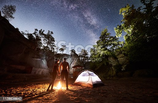 678554980istockphoto Couple tourists resting beside camp, campfire tent at night 1128638642