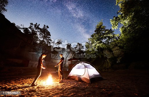 678554980 istock photo Couple tourists resting beside camp, campfire tent at night 1128638651