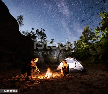 678554980 istock photo Couple tourists resting beside camp, campfire tent at night 1128638662