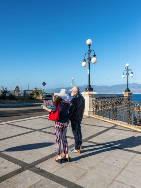 couple tourists traveling and using map - calabria map foto e immagini stock