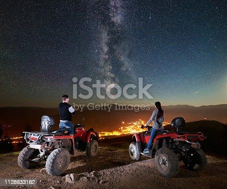 527894422 istock photo Couple tourists with atv quad bike under night starry sky 1128633162