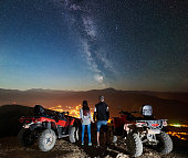 Rear view of boy and girl tourists with two atv quad motorbikes on the top of mountain, romantic couple enjoying beautiful view of night sky full of stars, Milky way, luminous town on background