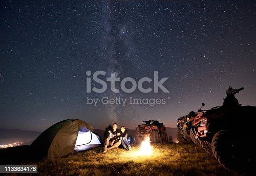 Happy couple man and woman trevelers sitting near tourist tent, burning campfire, three atv quad motorbikes on the top of mountain, enjoying beautiful view of night sky full of stars and Milky way