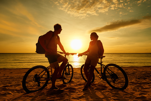 istock Couple tourists with Bicycles Watching Sunset. Silhouette people 468573946