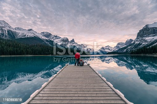 istock Couple traveler relaxing on wooden pier in Maligne lake at Spirit island, Jasper national park 1192893519