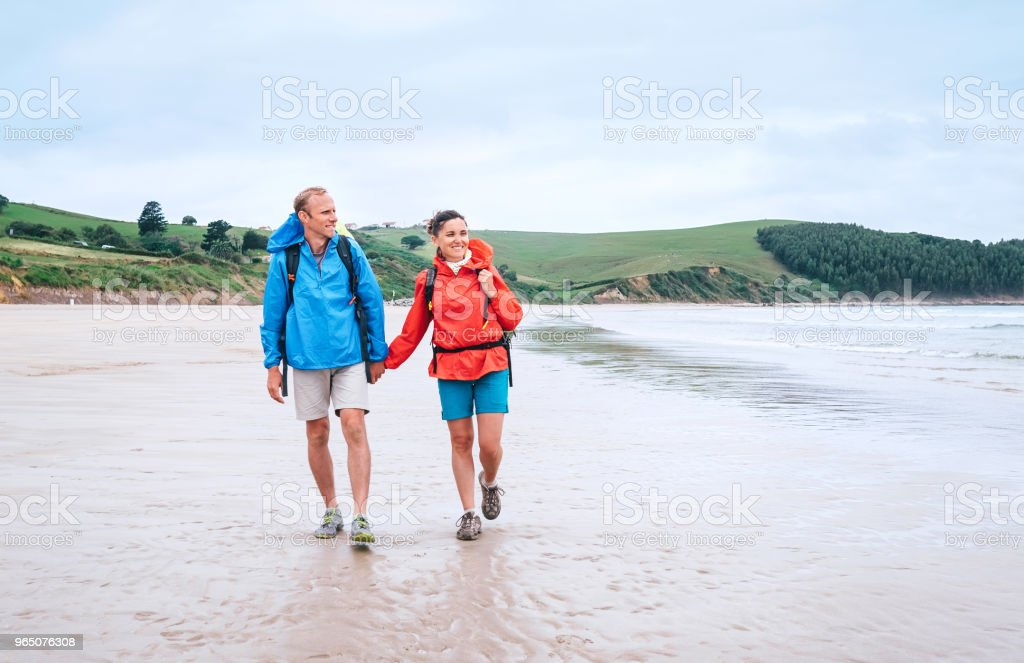 Couple travelers walk on the coast of Biskay Bay in North Spain, part of camino del Norte famous piligrims route zbiór zdjęć royalty-free