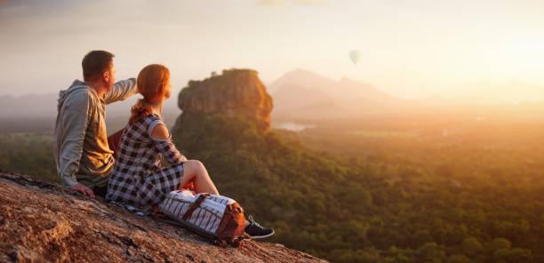 couple travelers watch beautiful sunset near famous rocky plateau Lion peak, Sigiriya. Sri Lanka stock photo