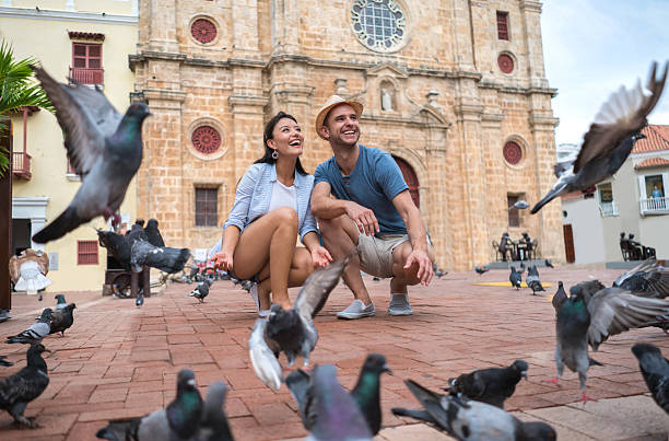 couple traveling and feeding doves in cartagena - voyages en amérique du sud photos et images de collection