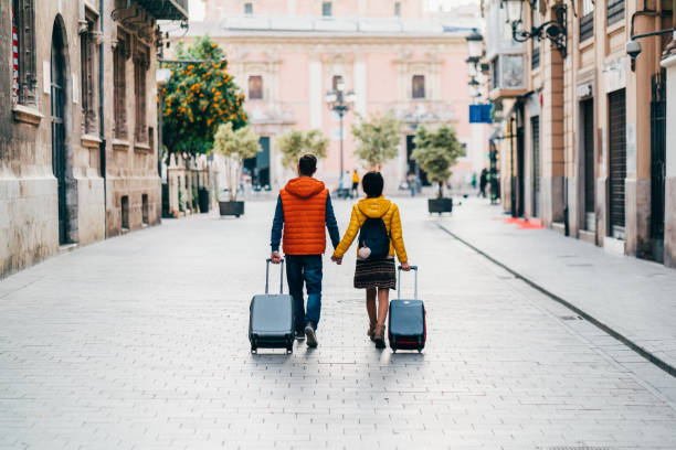 Couple traveling around the world Young couple with suitcases just arriving in Valencia travel stock pictures, royalty-free photos & images