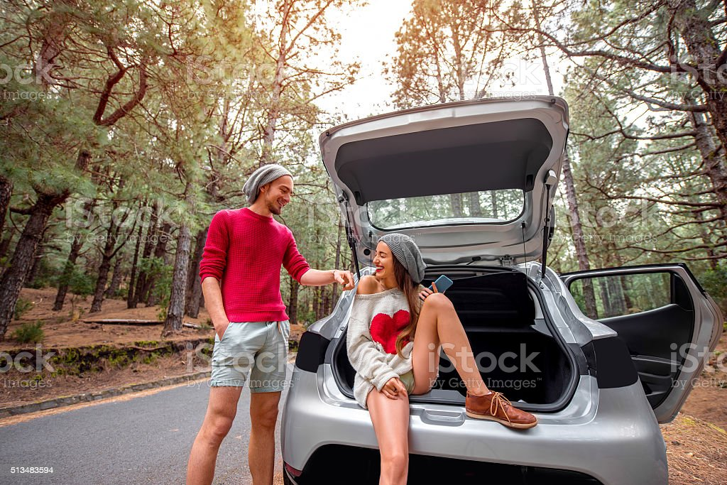 Couple traveling by car in the forest stock photo