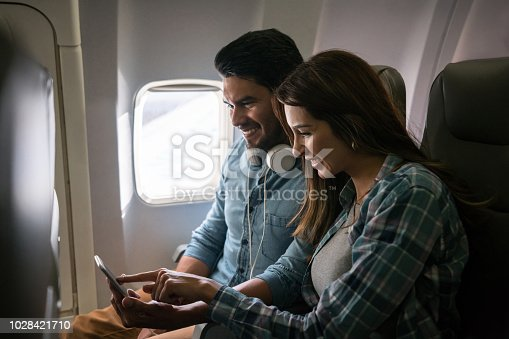 Happy Latin American couple traveling by plane and using their cell phone onboard on airplane mode - lifestyle concepts