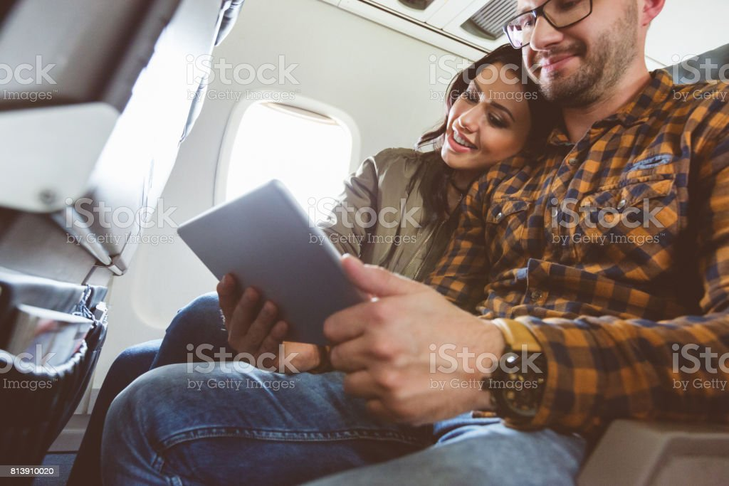 Couple traveling by plane using tablet pc stock photo