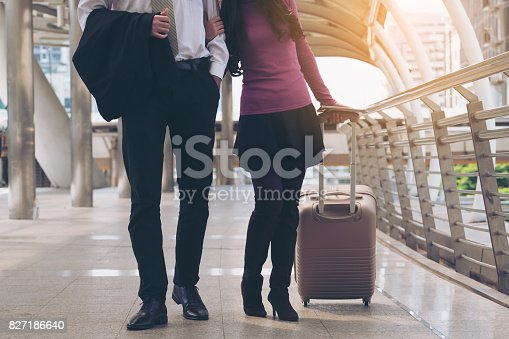 842907838 istock photo Couple travellers walking in airport walkway 827186640