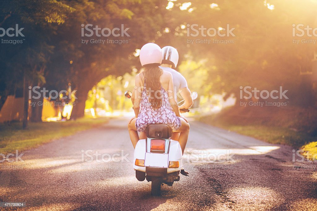 Couple travelling down a sunlit road on their scooter stock photo