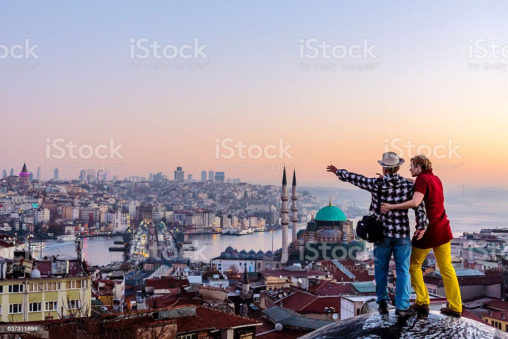 Couple travelling together staying on roof and overlooking cityscape stock photo