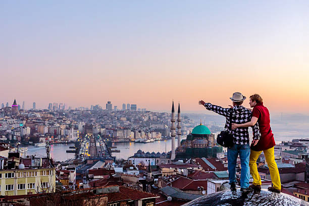 Couple travelling together staying on roof and overlooking cityscape – Foto