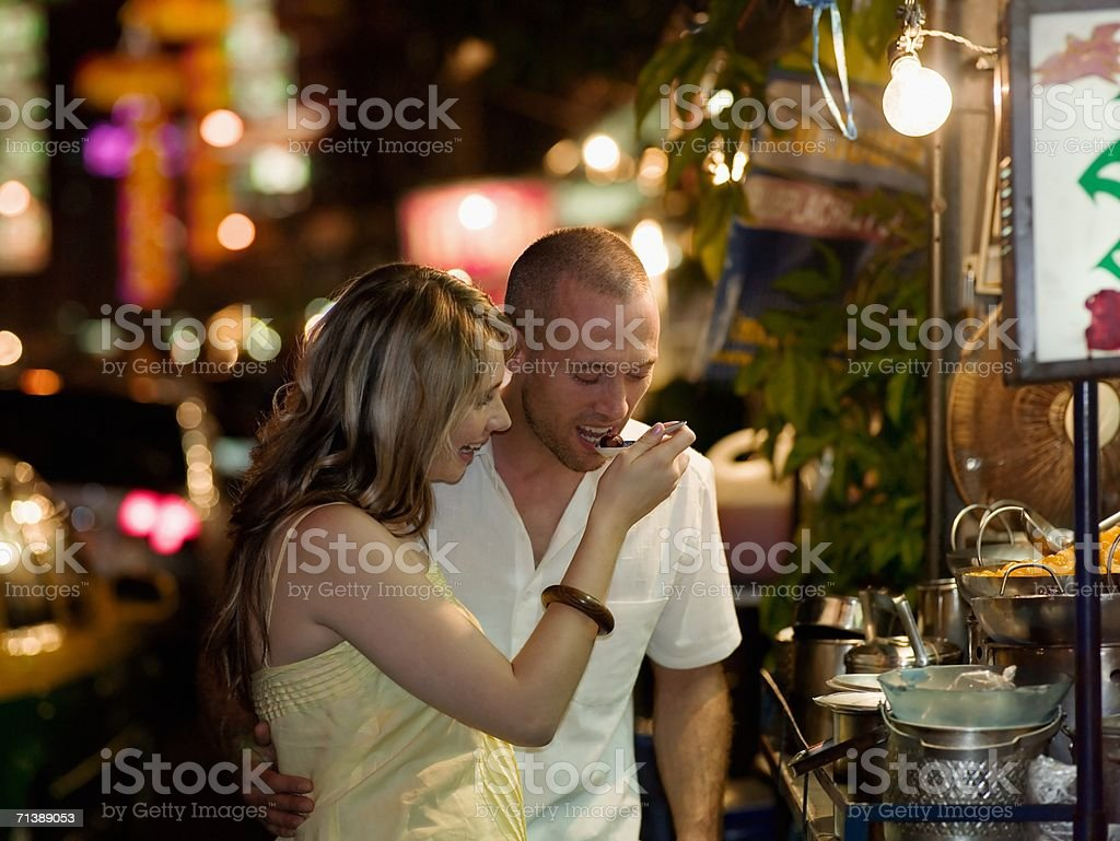 Couple trying food from street vendor stock photo