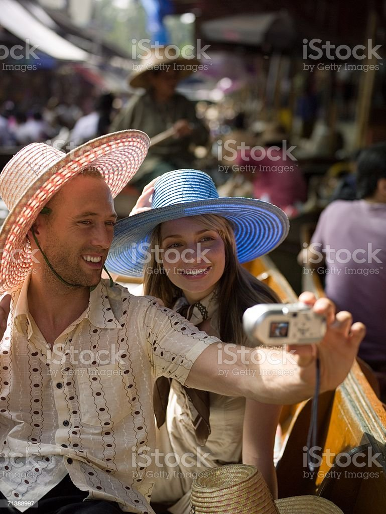 Couple trying on hats at floating market royalty-free stock photo