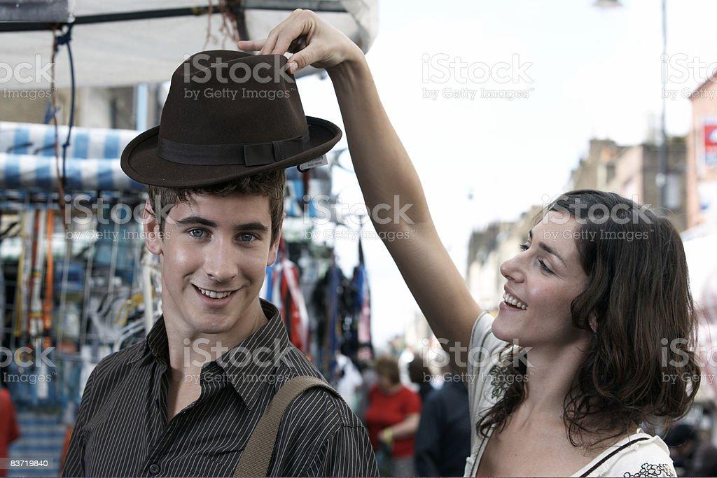 Couple trying on hats at market royaltyfri bildbanksbilder