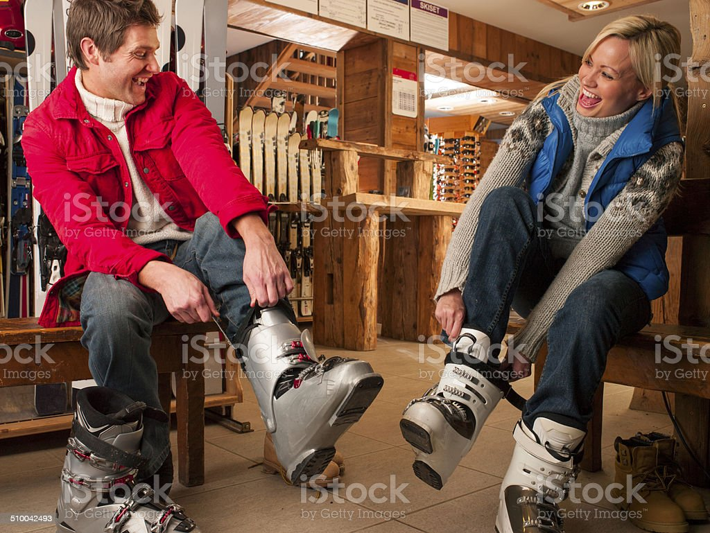 Couple Trying on Snow Boots stock photo