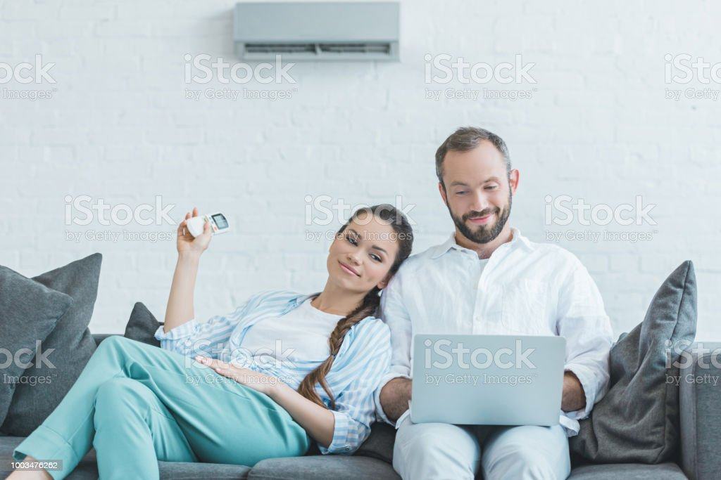 couple turning on air conditioner during the summer heat while using laptop stock photo
