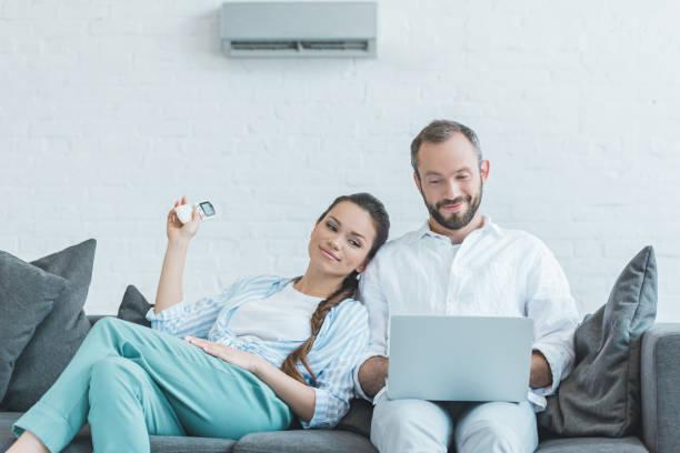 ノート パソコンを使用しながら夏の暑さにエアコンをオン カップル - エアコン ストックフォトと画像