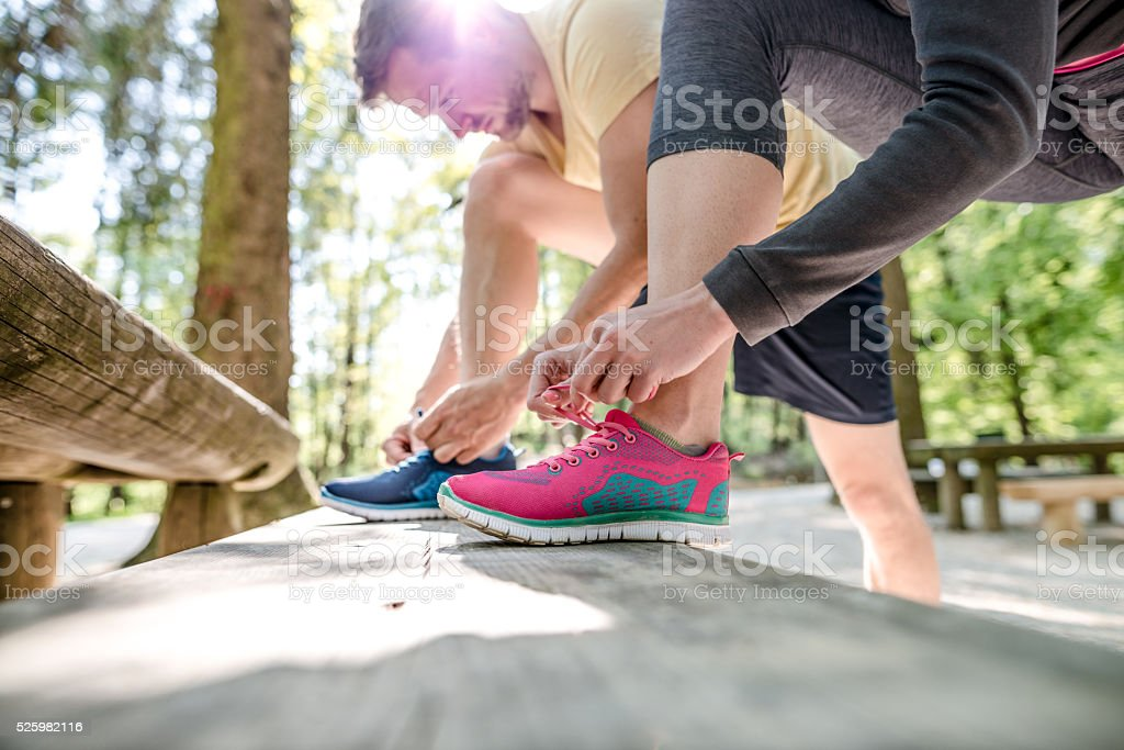 Couple tying shoes stock photo