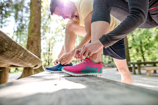Couple tying shoes stock photo