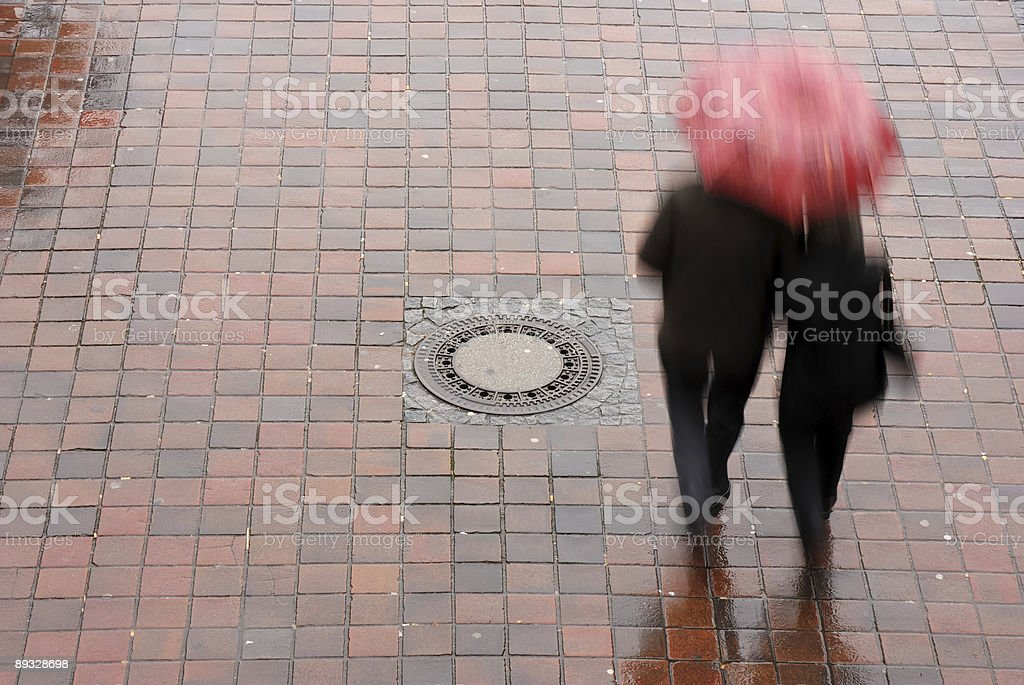 couple under a red umbrella, wet pavement stock photo
