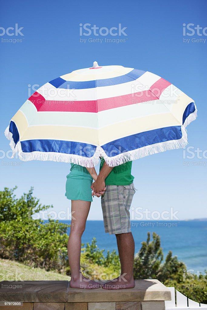 Couple under beach umbrella on patio overlooking ocean royalty-free stock photo