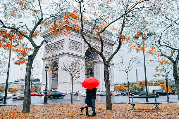 couple under umbrella at rain in paris - liebe auf französisch stock-fotos und bilder