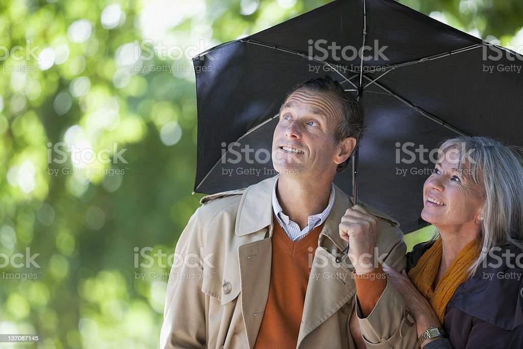 Couple under umbrella looking up royalty-free stock photo