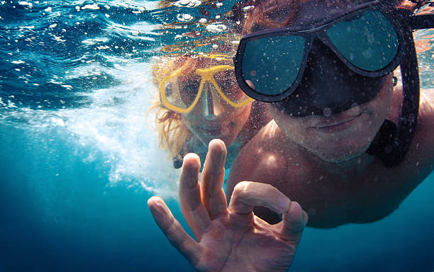 Couple underwater Young couple having fun underwater and showing ok sign snorkel stock pictures, royalty-free photos & images