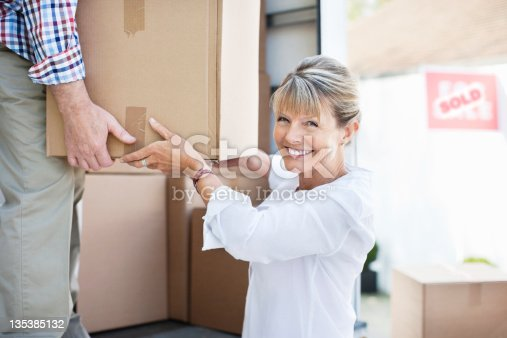 istock Couple unloading boxes from moving van 135385132