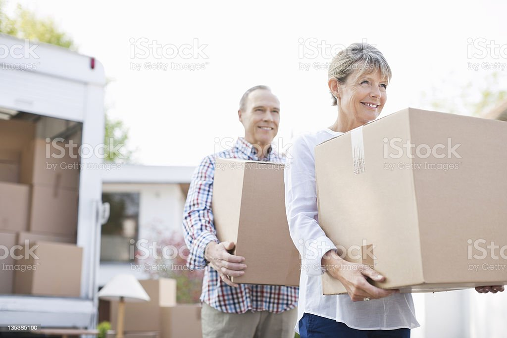 Couple unloading boxes from moving van​​​ foto