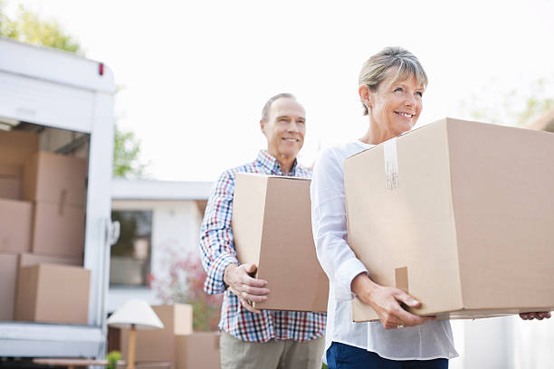 couple unloading boxes from moving van - physical activity stock photos and pictures