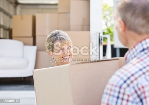 istock Couple unloading boxes from moving van 135385169