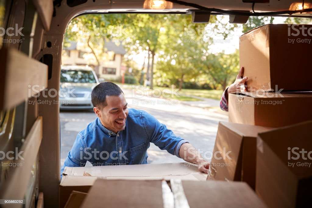 Couple Unloading Boxes From Van On Family Moving In Day stock photo
