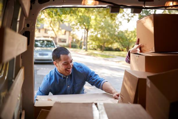 paar entladen boxen von van auf familie bewegt sich in tag - umzug transport stock-fotos und bilder
