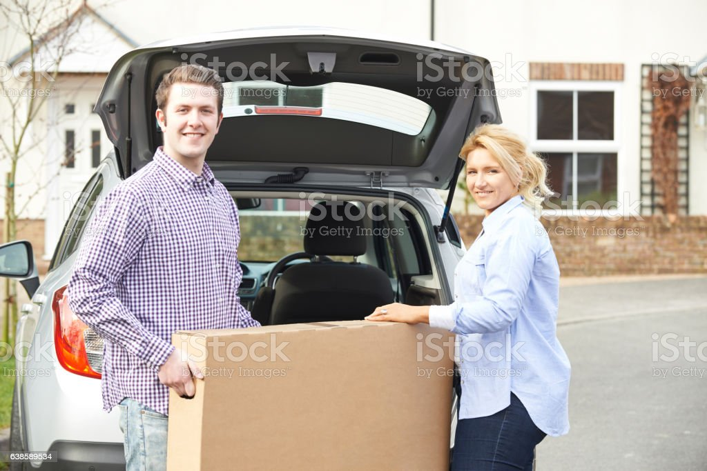 Couple Unloading New Television From Car Trunk stock photo