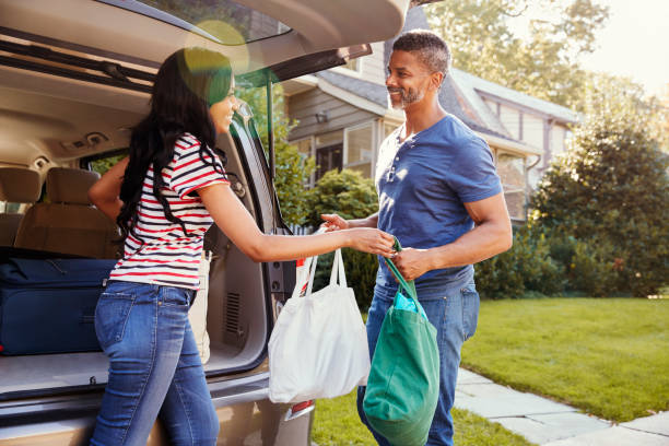 couple unloading shopping bags from car - grocery home foto e immagini stock