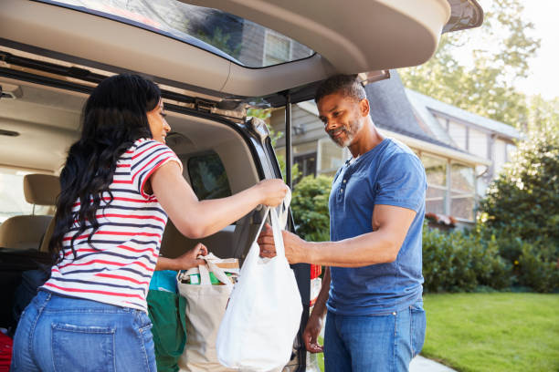 couple unloading shopping bags from car - carrying stock pictures, royalty-free photos & images