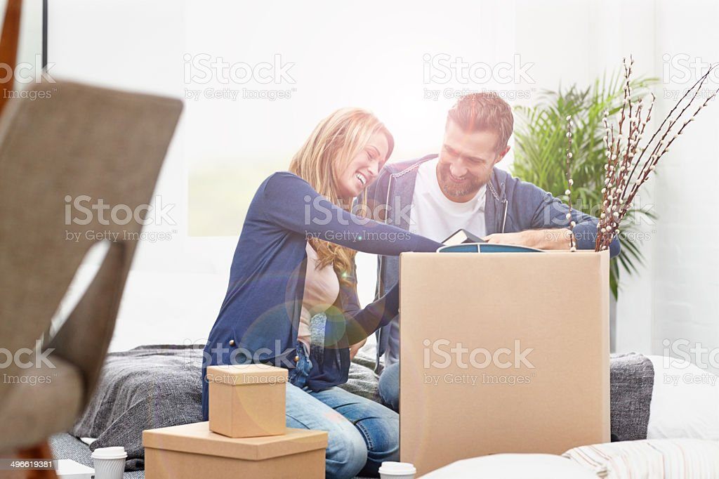 Couple unpacking boxes in their new home stock photo
