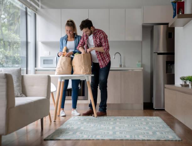 coppia che spacchetta generi alimentari a casa - grocery home foto e immagini stock