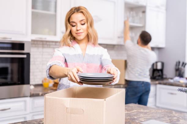 paar auspacken in küche - teller kaufen stock-fotos und bilder