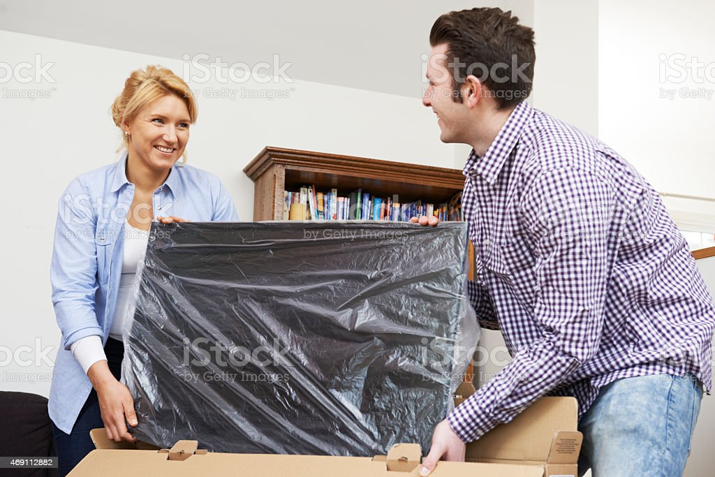Couple Unpacking New Television At Home stock photo