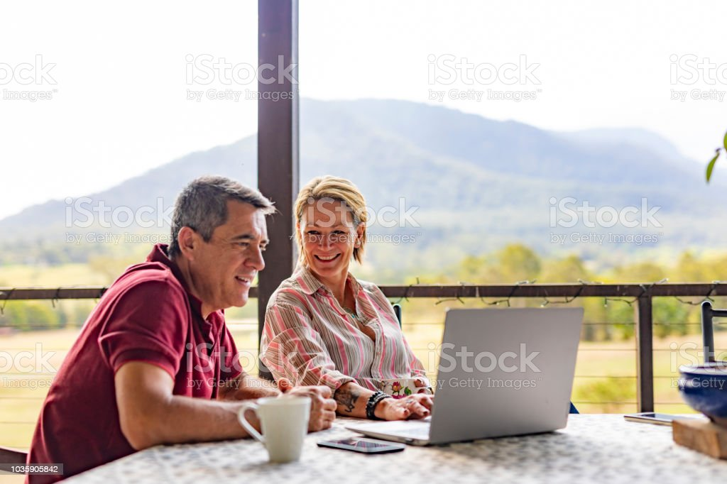 Couple Using a Computer at their Farm stock photo