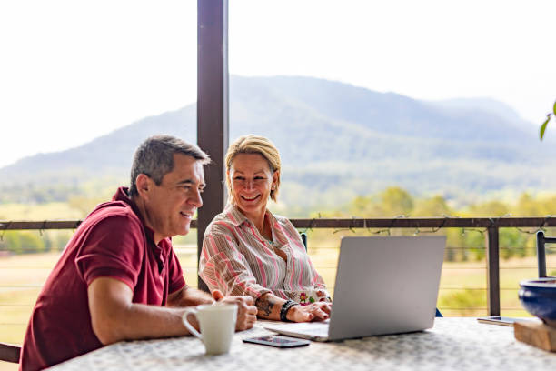 Couple Using a Computer at their Farm Mature couple using a laptop computer on the verandah of their farm in rural Australia rural scene stock pictures, royalty-free photos & images