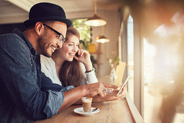 Couple using a digital tablet at coffee shop stock photo