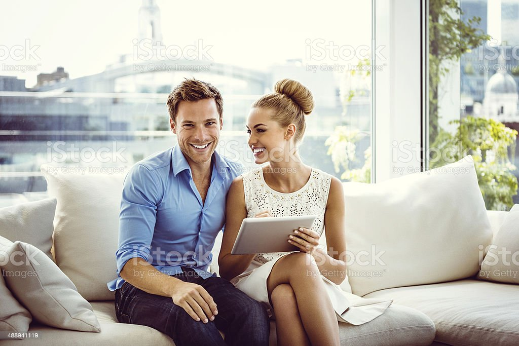 Couple using a digital tablet Smiling young couple sitting on sofa in an apartment and using digital tablet together. 25-29 Years Stock Photo